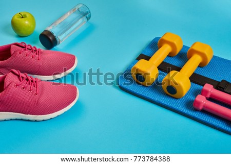 Healthy concept, diet plan with sport shoes and bottle of water and dumbbells on blue background, healthy food and exercise concept