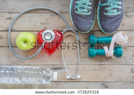 Healthy concept , diet plan with sport shoes and bottle of water and Dumbell on wooden background - stock photo