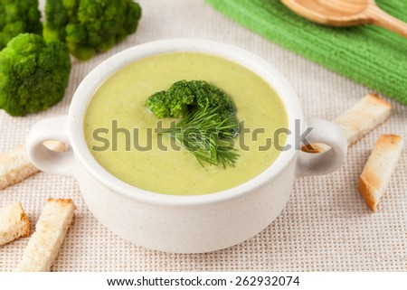 Healthy cream broccoli soup in a white dish on textile background - stock photo