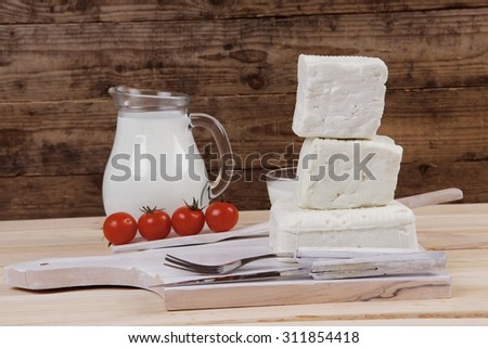 healthy dairy food fresh white greek goat sheep feta cheese on plate with milk in glass and full jug cherry tomatoes french bun over light wooden table with cutlery - stock photo