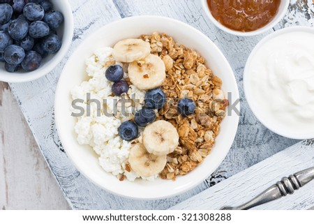 Healthy delicious breakfast with cottage cheese, muesli and fresh fruit, top view, horizontal - stock photo