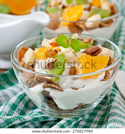 Healthy dessert with muesli and fruit in a glass bowl on the table - stock photo