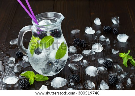 Healthy detox flavored water with blackberry and mint. Cold refreshing berry drink with ice on dark wooden table - stock photo