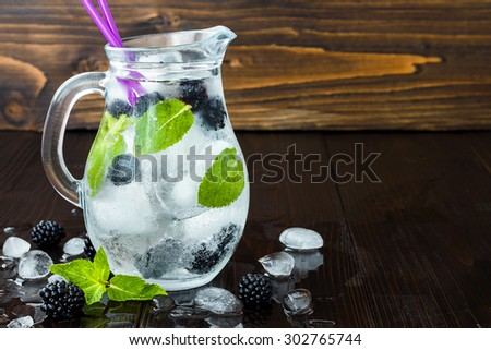 Healthy detox flavored water with blackberry and mint. Cold refreshing berry drink with ice on dark wooden table. Copy space background. Clean eating - stock photo