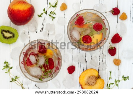 Healthy detox fruit infused flavored water. Top view. Summer refreshing homemade cocktail with fruits and thyme on white wooden table - stock photo