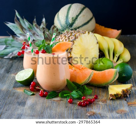 Healthy detox smoothie with fresh berries, tropical fruits and cantaloupe melon, shake for breakfast on wooden rustic background, summer harvest beverage, diet and vitamin concept - stock photo