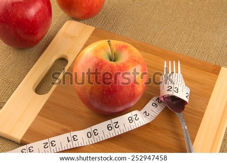 Healthy diet and nutrition for weight loss concept using apple and measuring tape - stock photo