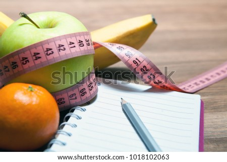 Healthy diet, fitness and weight loss concept. Measuring tape, notebook, apple on the table.