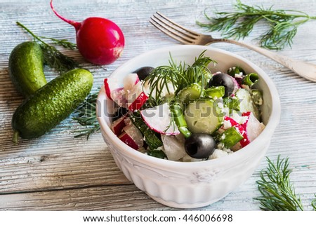 Healthy diet food: vegan vegetable salad with fresh cucumbers, radish, green onion, black olives, dill and feta cheese. In white ceramic bowl on light wooden background.  - stock photo