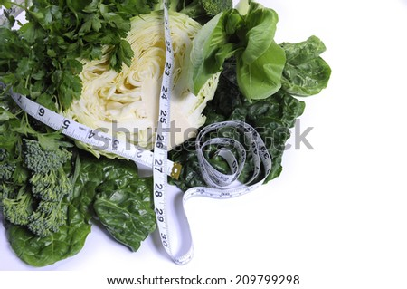Healthy diet health foods with leafy green vegetables including cabbage, broccoli, broccolini, parsley, celery, silverbeet, and spinach with measuring tape against a white background. - stock photo