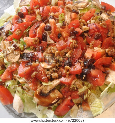 Healthy Diet Tomato Lettuce Walnut Raisins Salad sprinkled with Olive Oil Cumin and Pepper