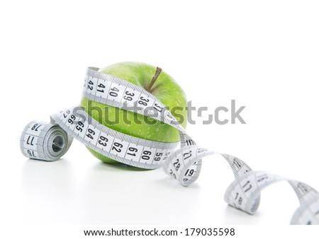 Healthy diet weight loss concept green apple and tape measure on a white background