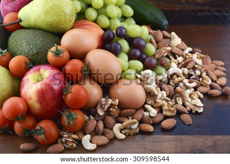 Healthy Diet with fresh fruit, apples, pears, avocados, grapes, eggs, nuts, tomatoes cucumbers on a rustic wood background. - stock photo