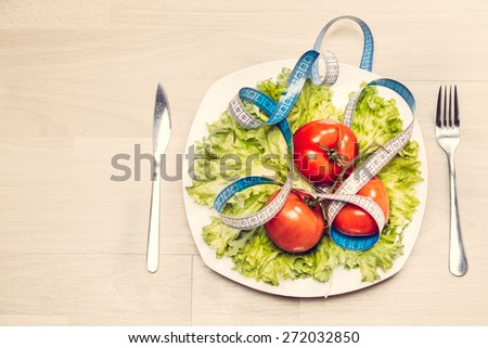 Healthy dieting and healthy lifestyle.Concept of diet,health and nutrition.Vibrant colorful vegetables on plate.Eating salad.Bright red tomatoes and lettuce diet meal with measuring tape  - stock photo