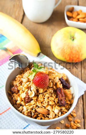 Healthy dreakfast with wholegrain muesli, fruits, nuts and milk over rustic wooden table