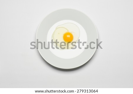 Healthy eating and Breakfast Topic: raw egg lays on a white plate on a white isolated background in studio top view - stock photo