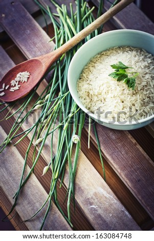 Healthy eating  background with bowls of rice and spices,fresh herbs,with green spring onions,bay leafs - stock photo