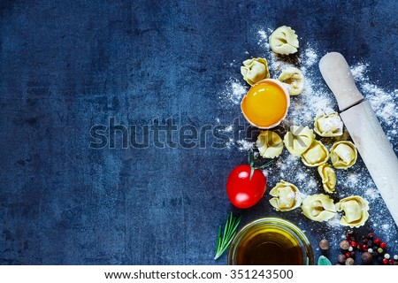 Healthy eating background with homemade Italian pasta tortellini, egg, tomatoes, flour, fresh herbs and olive oil on dark vintage texture. Food or cooking concept. Copy space. Top view. - stock photo