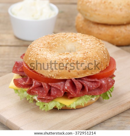 Healthy eating bagel sandwich for breakfast with salami ham, cream cheese, tomatoes and lettuce - stock photo