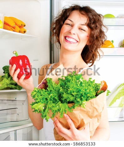 Healthy Eating Concept. Diet. Beautiful Young Woman near the Fridge with healthy food. Fruits and Vegetables in the Refrigerator. Vegan food