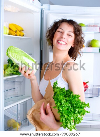 Healthy Eating Concept .Diet. Beautiful Young Woman near the Refrigerator with healthy food. Fruits and Vegetables