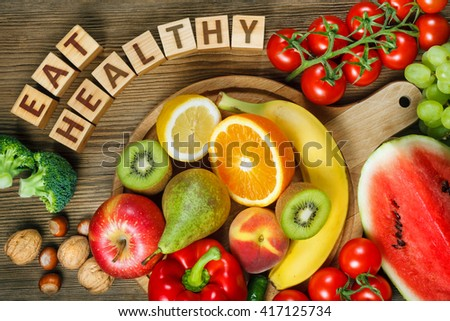 Healthy eating concept. Natural products rich in vitamins as oranges, lemons, red pepper, kiwi,tomatoes, bananas, pears, apples, walnuts, watermelon, hazelnuts, peach and green grape