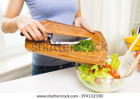 healthy eating, cooking, vegetarian food, diet and people concept - close up of woman adding chopped green onion to salad - stock photo
