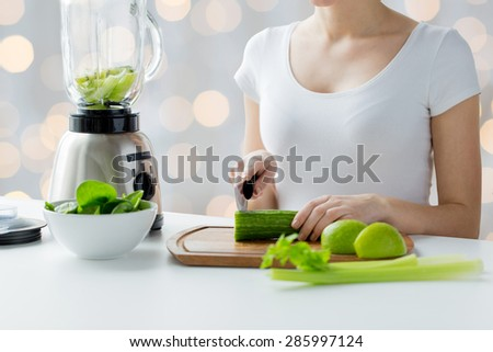 healthy eating, cooking, vegetarian food, dieting and people concept - close up of young woman with blender chopping green vegetables for detox shake or smoothie over holidays lights background - stock photo