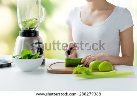 healthy eating, cooking, vegetarian food, dieting and people concept - close up of young woman with blender chopping green vegetables for detox shake or smoothie over natural background - stock photo