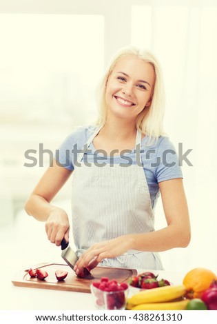 healthy eating, cooking, vegetarian food, dieting and people concept - smiling young woman chopping fruits and berries at home