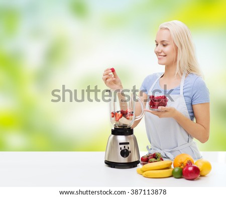 healthy eating, cooking, vegetarian food, dieting and people concept - smiling young woman putting fruits and berries for fruit shake to blender shaker over green natural background