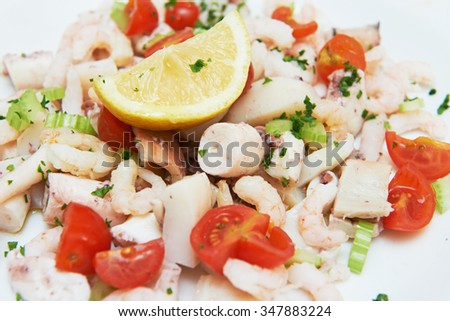healthy eating. delicious seafood salad with shrimp octopus squid and tomatoes lemon  - stock photo