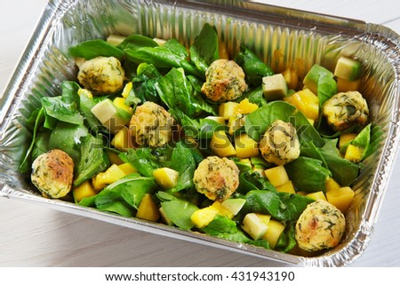 Healthy eating, diet concept. Creative healthy food. Healthy vegetarian lunch, Take away organic food. Weight loss diet, food take away in aluminium box. Falafel with mango cubes and spinach, closeup - stock photo