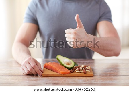 healthy eating, diet, gesture and people concept - close up of male hands showing thumbs up with food rich in protein on cutting board on table - stock photo