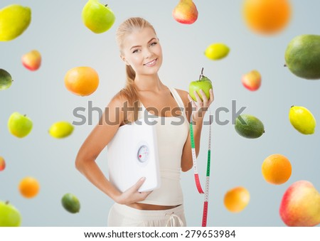 healthy eating, diet, weight control and people concept - happy young woman with scale, green apple and measuring tape over gray background with falling fruits - stock photo