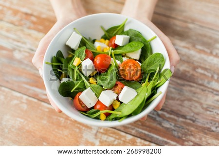 healthy eating, dieting and people concept - close up of young woman hands showing salad bowl at home - stock photo