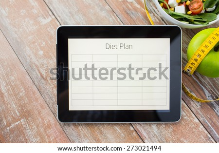 healthy eating, dieting and weigh loss concept - close up of diet plan on tablet pc screen, green apple, measuring tape and salad - stock photo