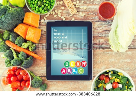 healthy eating, dieting, calories counting and weigh loss concept - close up of tablet pc screen with chart and vegetables on table - stock photo