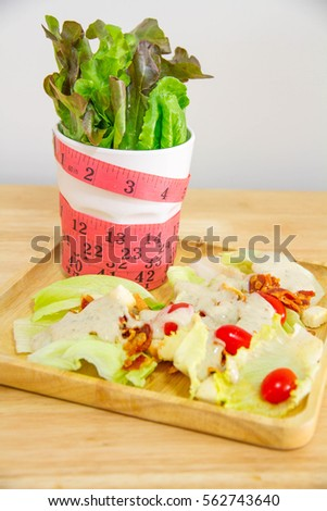 healthy eating, dieting, slimming and weigh loss concept - close up of diet, measuring tape and salad