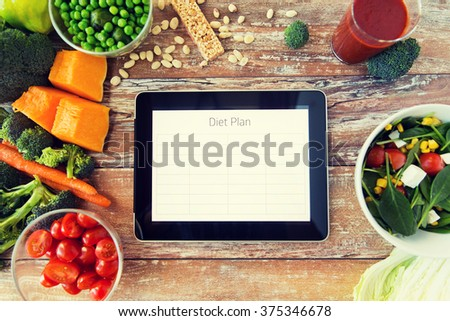 healthy eating, dieting, slimming and weigh loss concept - close up of diet plan on tablet pc screen and vegetables - stock photo