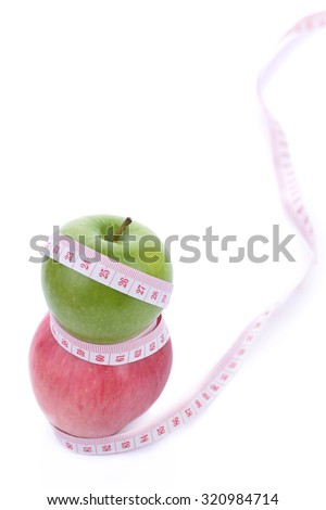 healthy eating, dieting, slimming and weigh loss concept - close up of green apple, measuring tape
