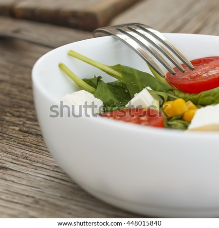 Healthy eating, dieting, vegetarian food and cooking concept - close up of vegetable salad bowl and fork at home