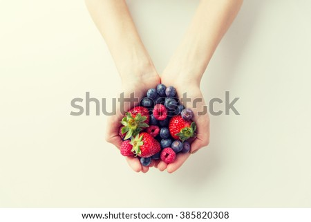 healthy eating, dieting, vegetarian food and people concept - close up of woman hands holding berries at home - stock photo