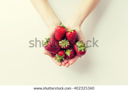 healthy eating, dieting, vegetarian food and people concept - close up of woman hands holding strawberries at home - stock photo