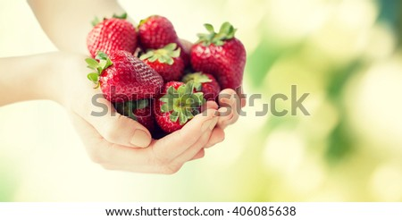 healthy eating, dieting, vegetarian food and people concept - close up of woman hands holding ripe strawberries over green natural background - stock photo
