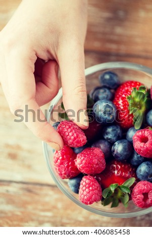 healthy eating, dieting, vegetarian food and people concept - close up of woman hands with berries mix in glass bowl on wooden table - stock photo