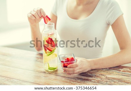healthy eating, drinks, diet, detox and people concept - close up of woman with fruit water in glass bottle - stock photo