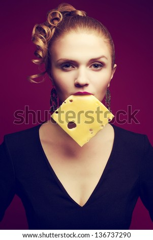 Healthy eating. Food concept. Arty portrait of fashionable young woman holding cheese slice in her mouth and posing over purple (pink) background. Avant-garde style. Studio shot - stock photo