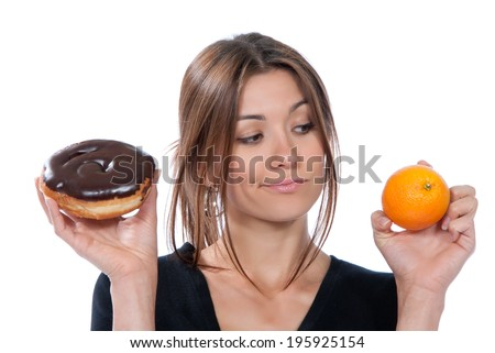 Healthy eating food concept. Woman comparing unhealthy donut and orange fruit, thinking isolated on a white background - stock photo