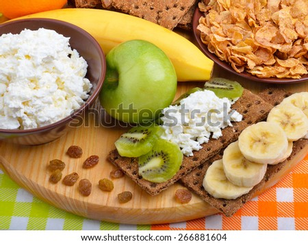 Healthy eating. Fresh fruit, cornflakes and dry loaves with curd on a wooden background - stock photo